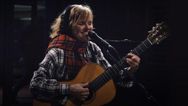 Diane Tell est souriante en chantant et en jouant de la guitare dans le studio de Tellement Courteau.