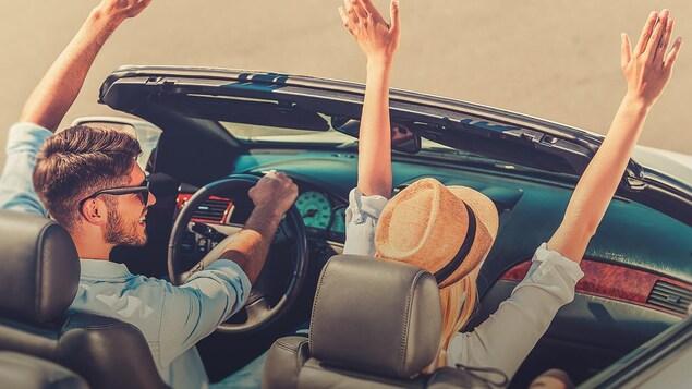 Un couple dans une voiture décapotable lèvent les bras.