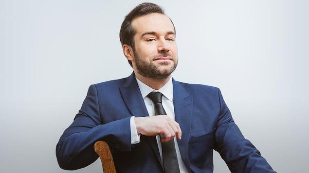 Fabien Gabel est assis sur une chaise, il porte un complet bleu.