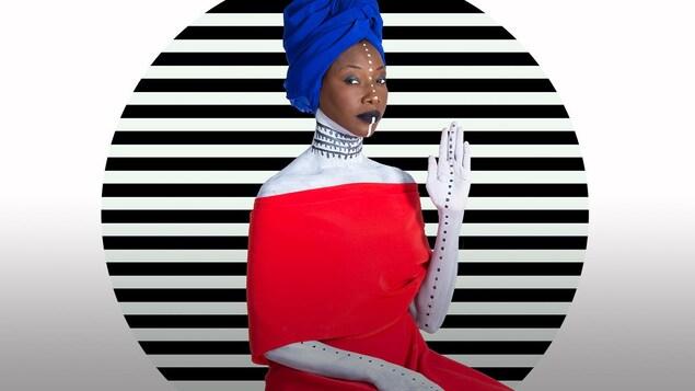 La chanteuse malienne Fatoumata Diawara prend la pose dans une robe rouge saillante devant un fond blanc ligné noir.