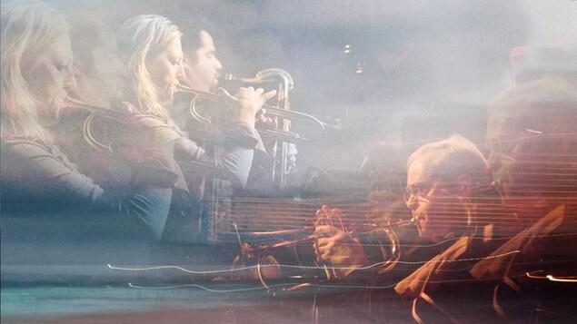 De gauche à droite une femme jouant de la trompette, un homme jouant du saxophone et un homme jouant de la trompette