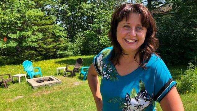 Isabelle Beaudin, agente de développement au service loisirs et culture pour la Ville de Baie-Comeau, dehors, dans une cour remplie de verdure.