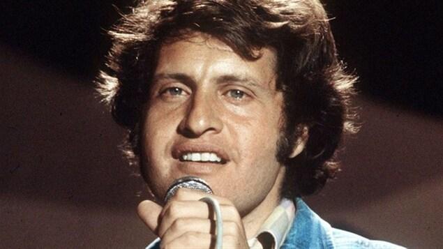 Gros plan sur le visage de Joe Dassin en train de chanter, micro à la main.