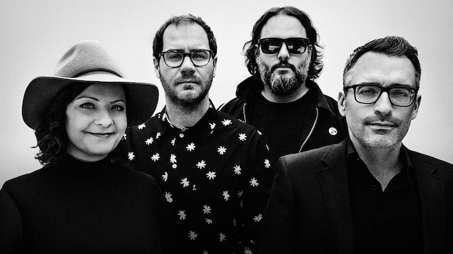 Une femme et trois hommes posent un à côté de l'autre pour une photo en noir et blanc.