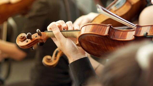Gros plan sur les mains et l'instrument d'un violoniste classique vu de côté.