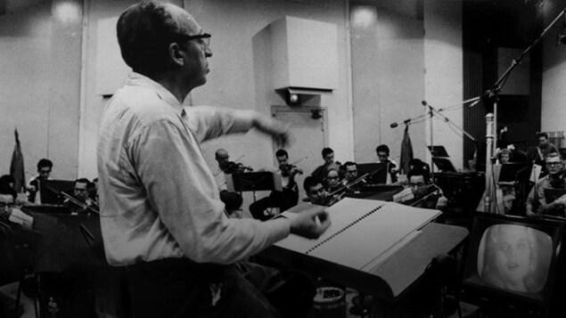 Le compositeur Aaron Copland dirige la musique d'un film en 1961 à Paris.