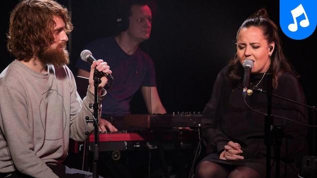 Ariane Moffatt et Philippe Brach assis l'un à côté de l'autre sur scène devant un claviériste; ils chantent.