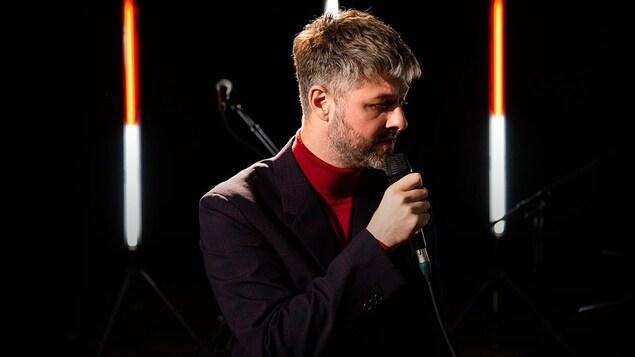 On le voit, seul au micro. Il porte un veston sur un col roulé rouge.