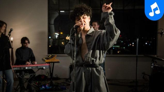 L'artiste offre une prestation avec ses musiciens.