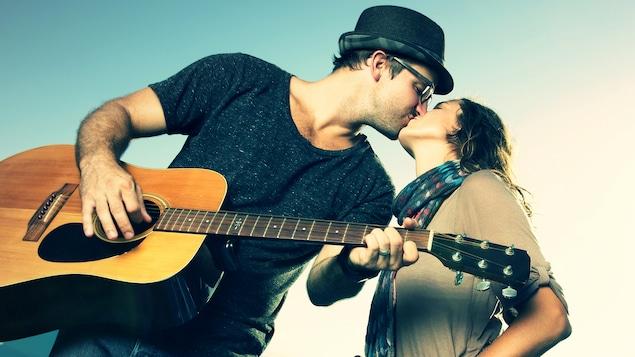Un couple s'embrasse. Le jeune homme porte un chapeau et tient une guitare.