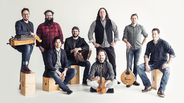 Les membres des groupes Le Vent du Nord et De Temps Antan qui posent devant un arrière-plan blanc, certains d'entre eux tenant des instruments