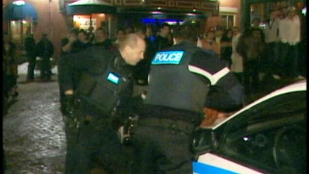 Deux policiers tentent de maîtriser quelqu'un à proximité de leur véhicule alors que plusieurs passants observent la scène.