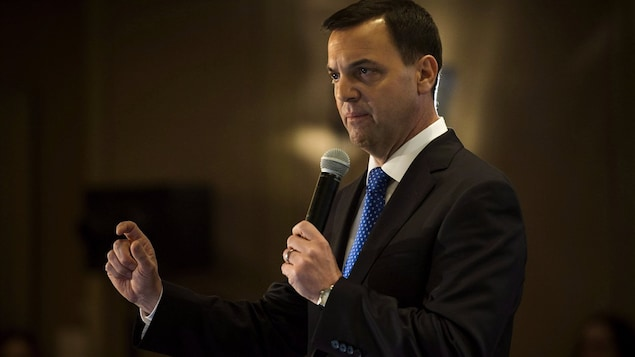 Un homme en complet tient un microphone.