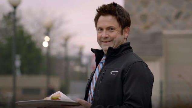 Un homme tient dans une assiette des burgers.