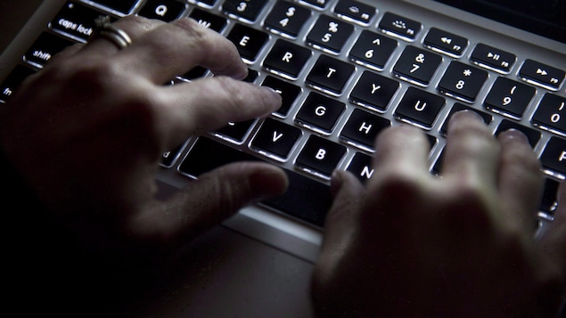 Des mains sur un clavier d'ordinateur.