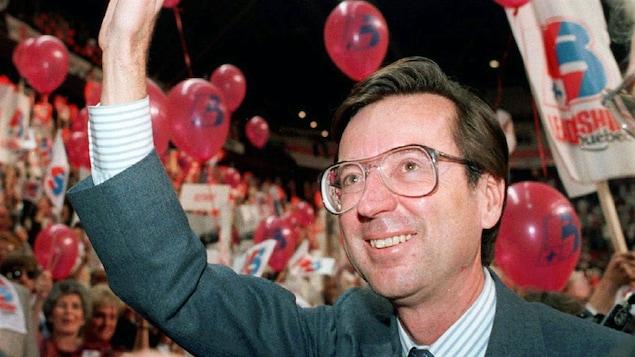 Portrait de Robert Bourassa qui salue une foule dans un ongrès du Parti libéral.