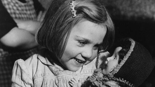 Une petite fille reçoit une poupée en 1946.