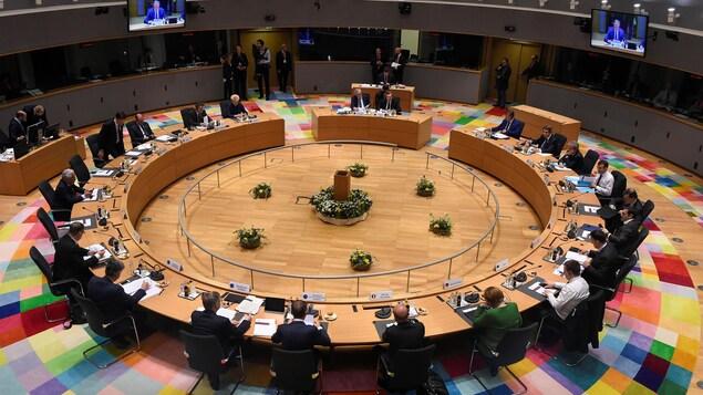 Dans un parlement, des députés sont assis sur une table circulaire.
