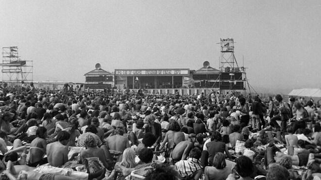 Une foule de hippies devant une scène de festival.