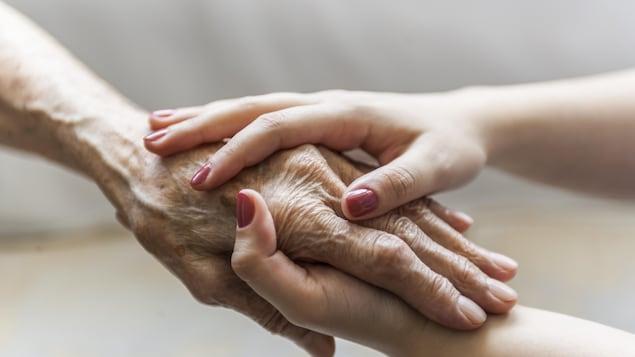 Une femme plus jeune tient la main d'une femme âgée.