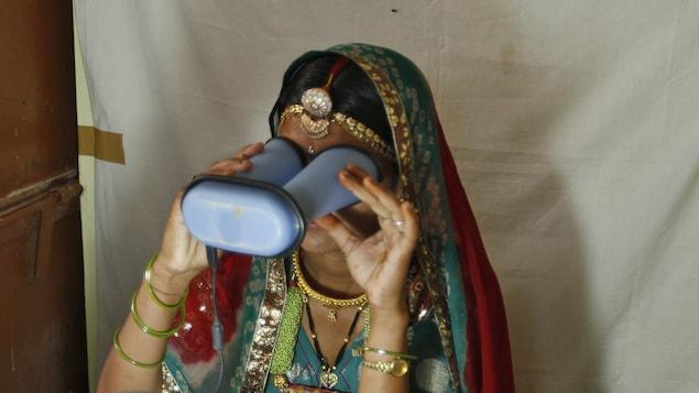 Une dame vêtu d'un habit traditionnel indien tient un appareil devant ses yeux.