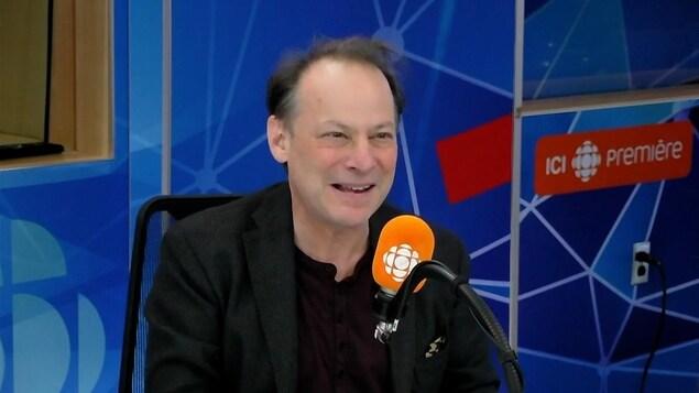Adam Gopnik derrière un micro dans un studio radio de Radio-Canada.