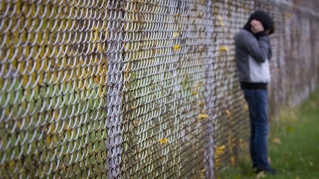Un adolescent appuyé sur une clôture se bouche les oreilles.