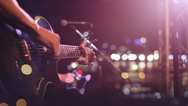 Un musicien joue de la guitare sur scène.