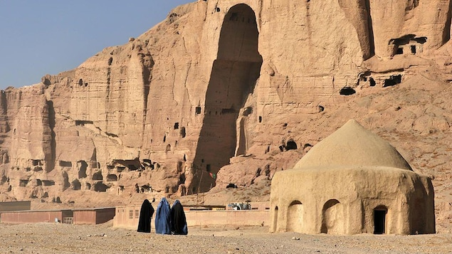 Des femmes en burqa se tiennent debout devant les bouddhas détruient dans la vallée de Bâmiyân
