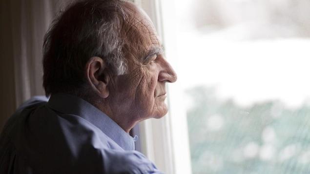 Un homme âgé seul regarde depuis une fenêtre vers l'extérieur.