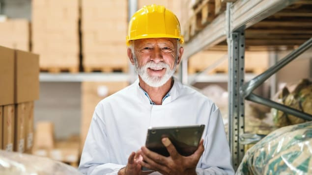 Un homme d'une soixantaine d'année pose dans les allées d'un entrepôt, un casque sur la tête et une tablette dans les mains.