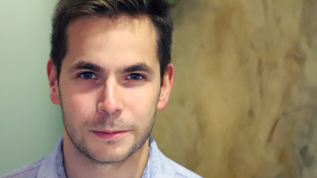 Le visage d'un homme qui regarde directement la caméra.