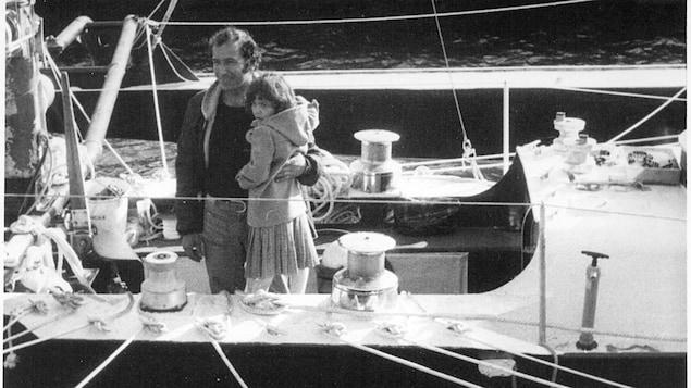 La photo en noir et blanc d'un marin et d'un enfant sur un bateau.