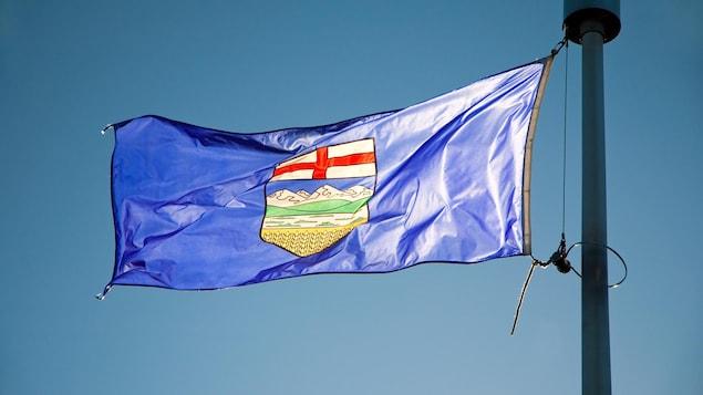 Le drapeau de l'Alberta flotte au vent.
