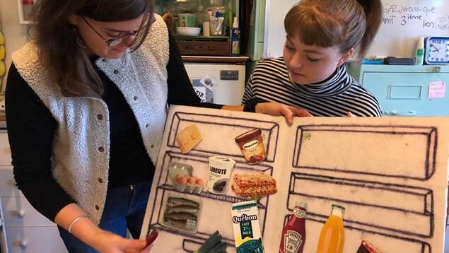 Une femme et une jeune fille regardent un dessin représentant l'intérieur d'un réfrigérateur
