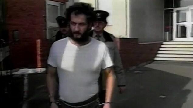 Allan Legere menotté et amené par deux policiers à son procès.