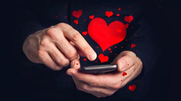 Un homme tient dans ses mains un cellulaire duquel s'échappent des cœurs rouges.