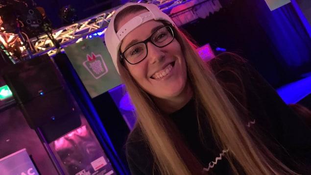 Une femme sourit à la caméra alors qu'on peut voir une affiche de festival Juste pour rire en arrière-plan.