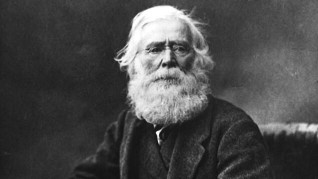 Le géologue Sir William Logan assis sur une chaise, une plume à la main et regardant l'objectif.