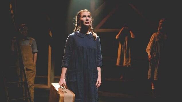 Une femme débout regarde vers l'horizon dans le noir. Une de lumière qui vient d'en haut illumine son visage. Elle tiens une valise à la main droite. Elle se trouve sur la scène. Au fond, trois personnes la regarde.