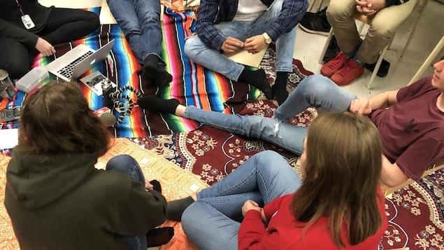 Des jeunes sont assis en rond sur des tapis