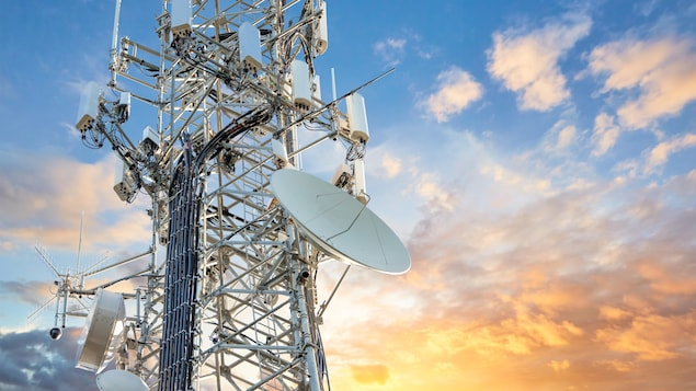 Une tour de transmission 5G, devant un coucher de soleil.