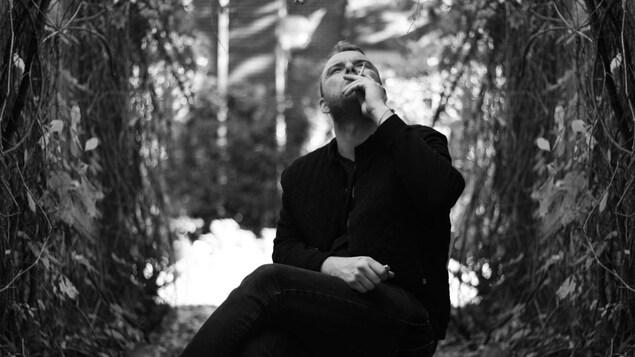 Anthony Roussel, auteur-compositeur-interprète, assis sur une chaise en bois dehors, dans un sentier avec des arbres.