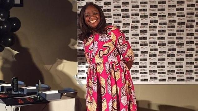 Une femme souriante porte une longue robe rose et jaune faite de tissu au motif africain.