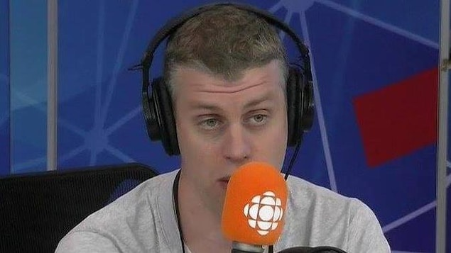 Un homme devant un micro de Radio-Canada.