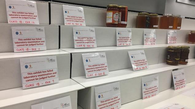 Sur les étagères où sont exposés les miels inscrits au concours des Prix mondiaux de l'apiculture, des affiches écrites en rouge remplacent les miels qui ont échoué les test de qualité.  Il y a davantage d'affiches que de pots de miels.  Près de la moitié des miels ont été disqualifiés