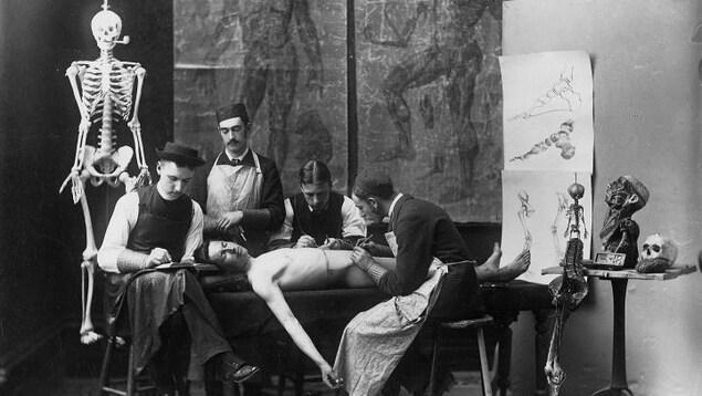Photo en noir et blanc montrant quatre hommes en train d'examiner un cadavre.