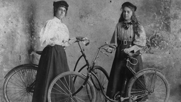 Photographie en noir et blanc montrant deux jeunes femmes tenant chacune un vélo.