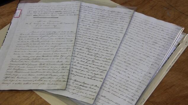 Des documents d'archives écrits à la main sur un comptoir en bois.
