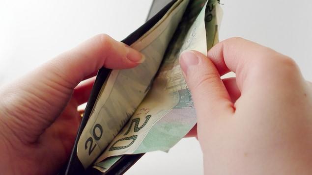 Un portefeuille rempli de billets de 20 dollars.